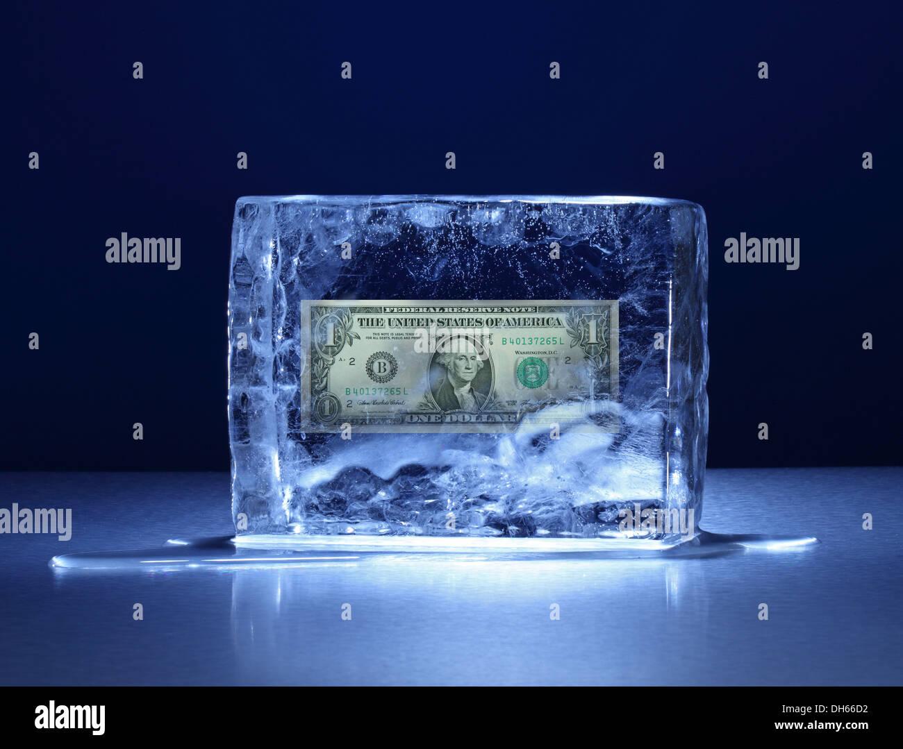 Un dollaro US banconota congelati in un chiaro blocco di ghiaccio Immagini Stock