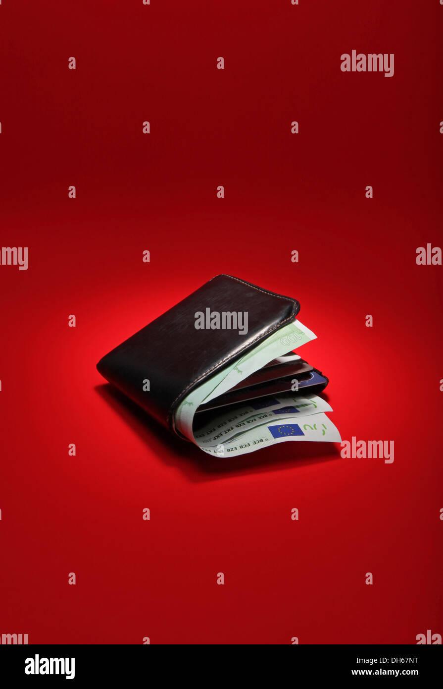 Un nero portafoglio in pelle riempito con moneta europea su un brillante sfondo rosso Immagini Stock