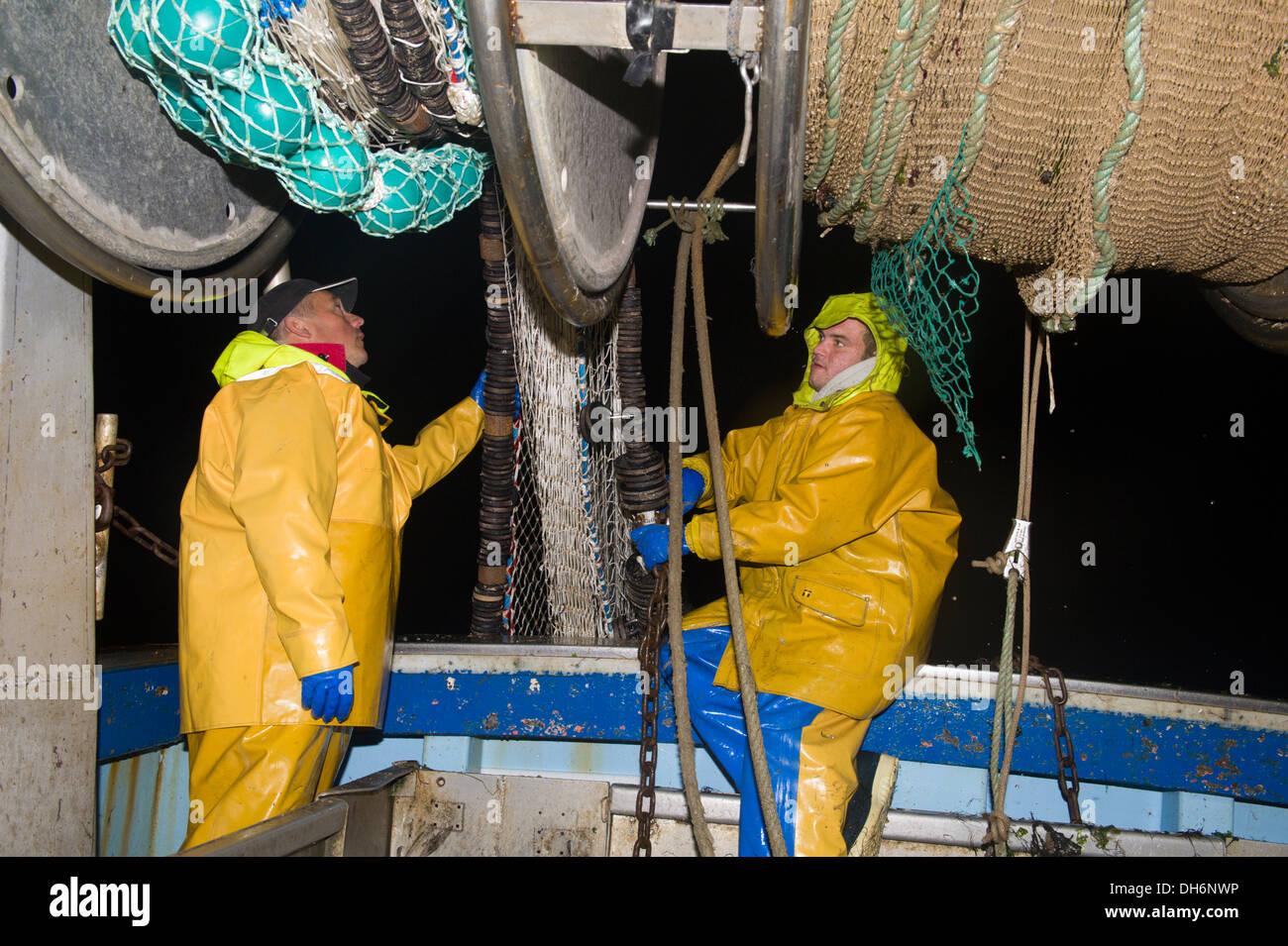 Due pescatori sono la visione di reti a strascico per essere innalzato Immagini Stock