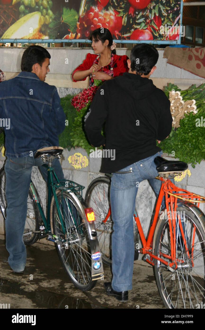 Signora tradizionali vendono spezie in Samarcanda, Uzbekistan a due uomini in bici Immagini Stock