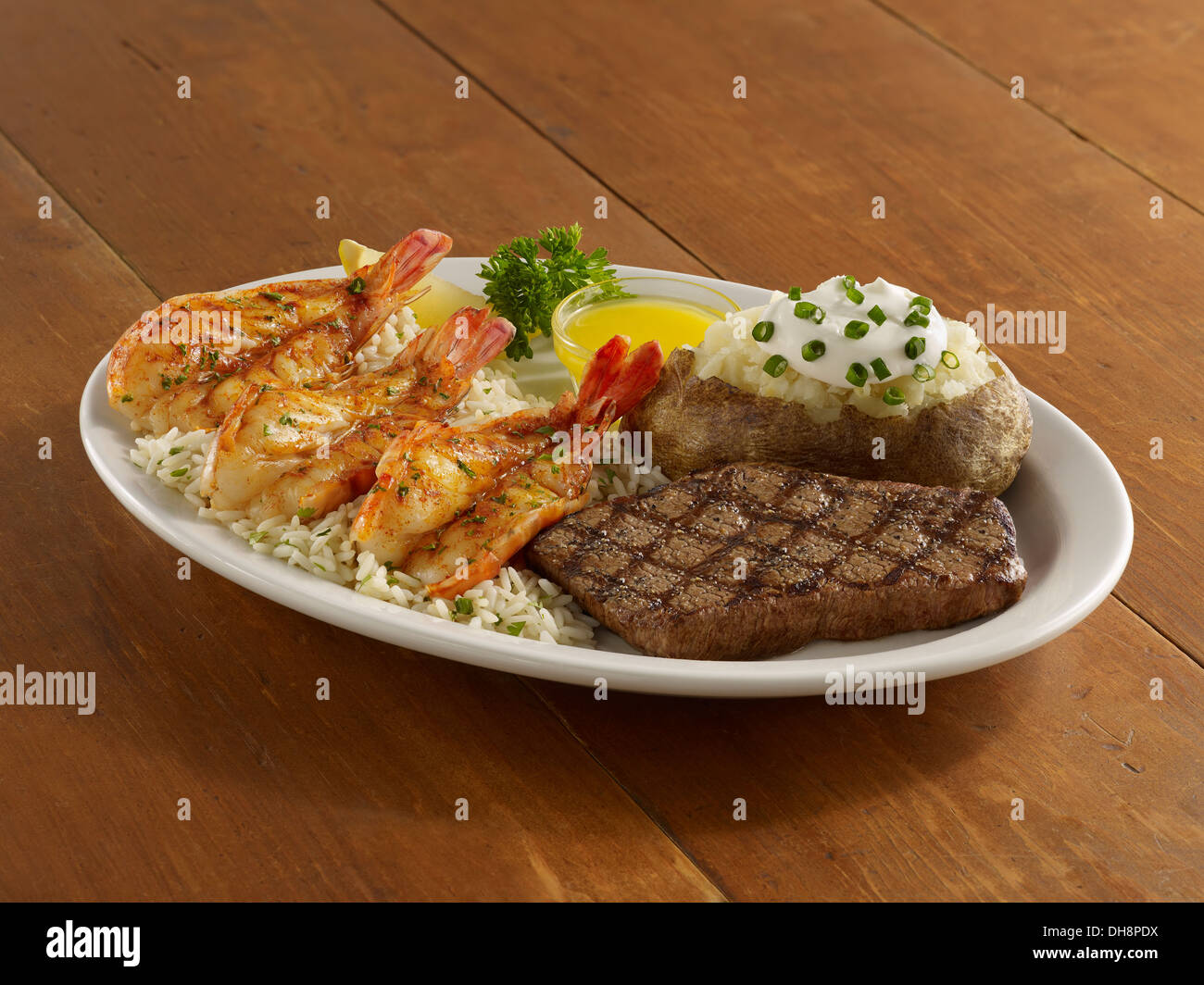 Grigliata di gamberi e bistecca con patate al forno Immagini Stock