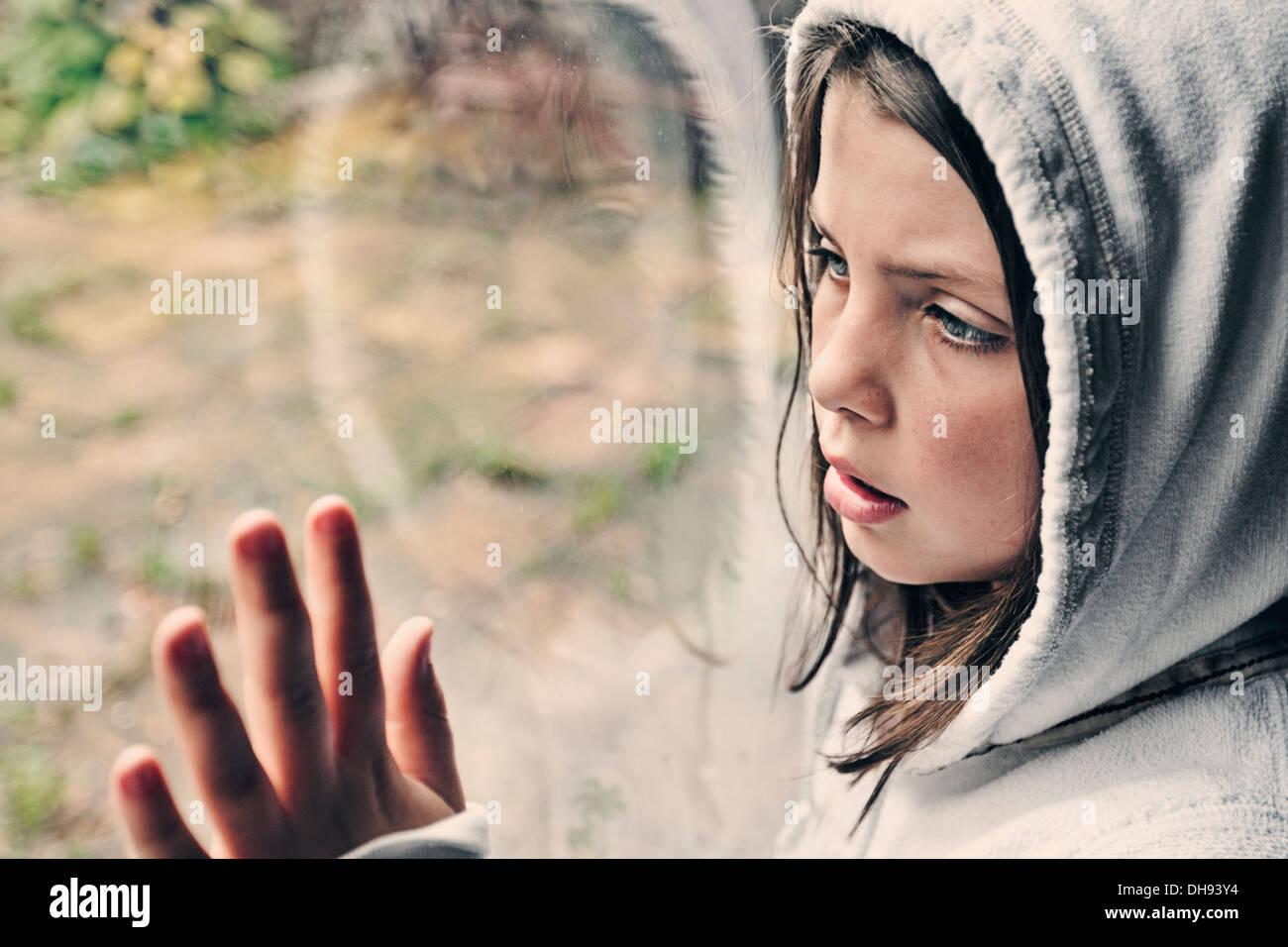 Ragazza giovane guardando fuori della finestra Immagini Stock