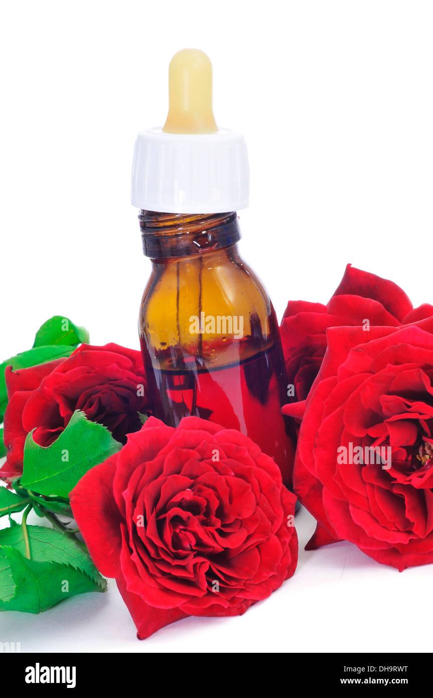 Primo piano di un flacone contagocce con essenza di rose con rose rosse sullo sfondo Immagini Stock