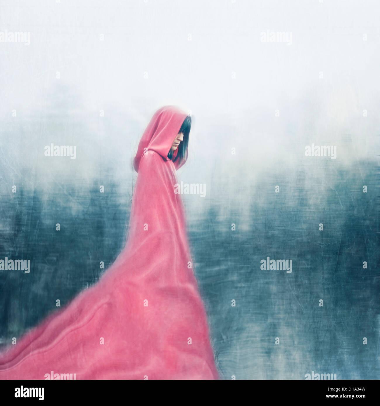 Donna che indossa red cape passeggiate all'aperto Immagini Stock