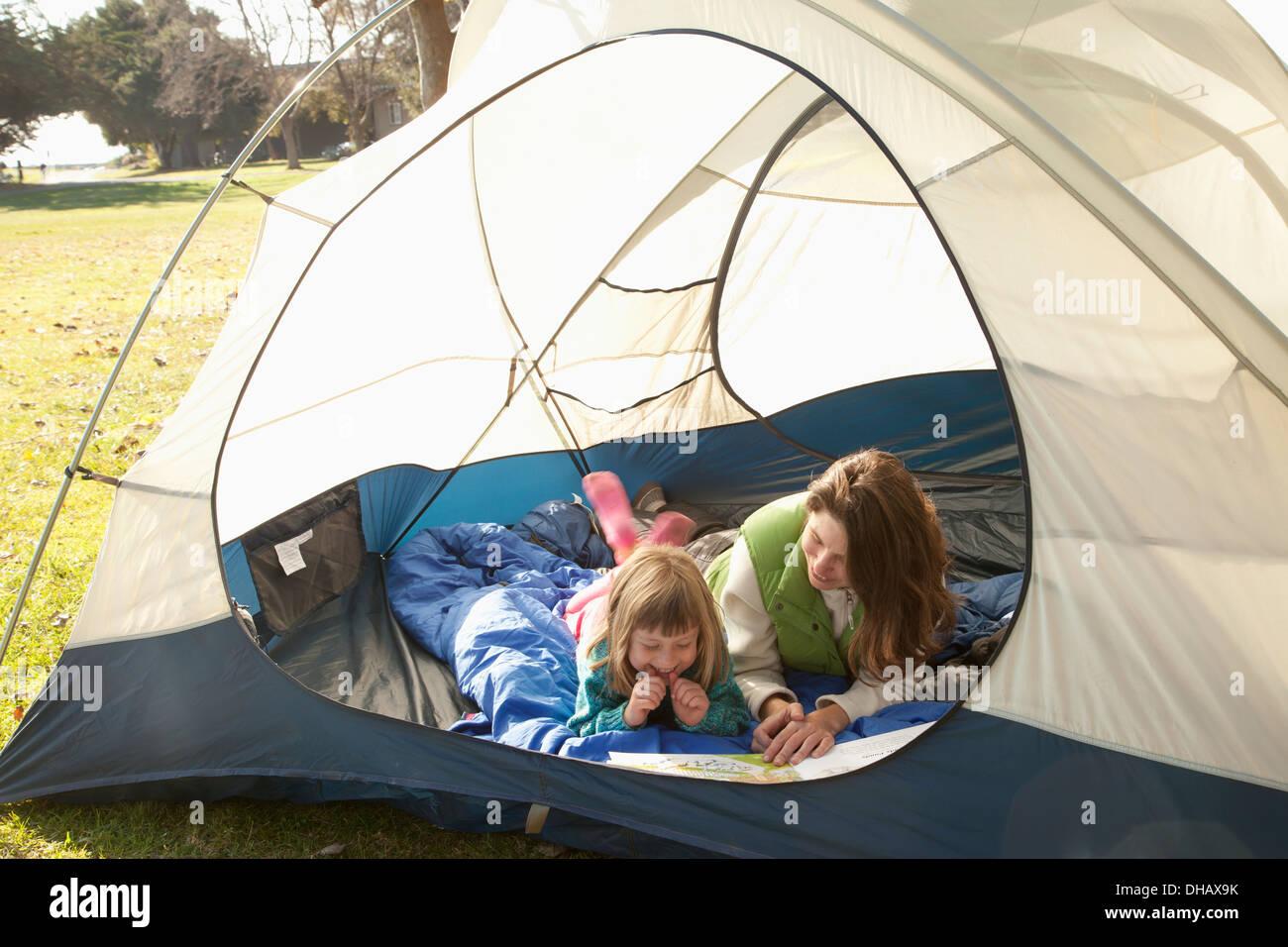 Una madre e figlia laici in una tenda la lettura di un libro; Crab Cove, Alemada, California, Stati Uniti d'America Immagini Stock