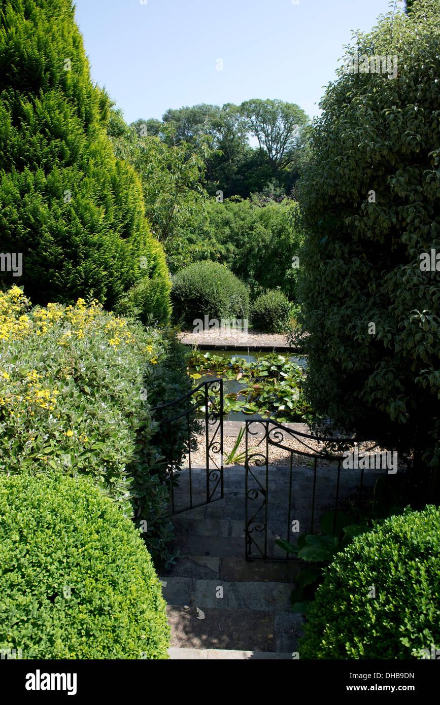 Giardino passi attraverso gli arbusti che conduce verso il basso attraverso un cancello ad un laghetto Immagini Stock