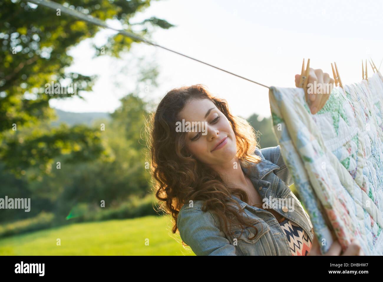 Una donna panni appesi sulla linea di lavaggio, nell'aria fresca. Immagini Stock