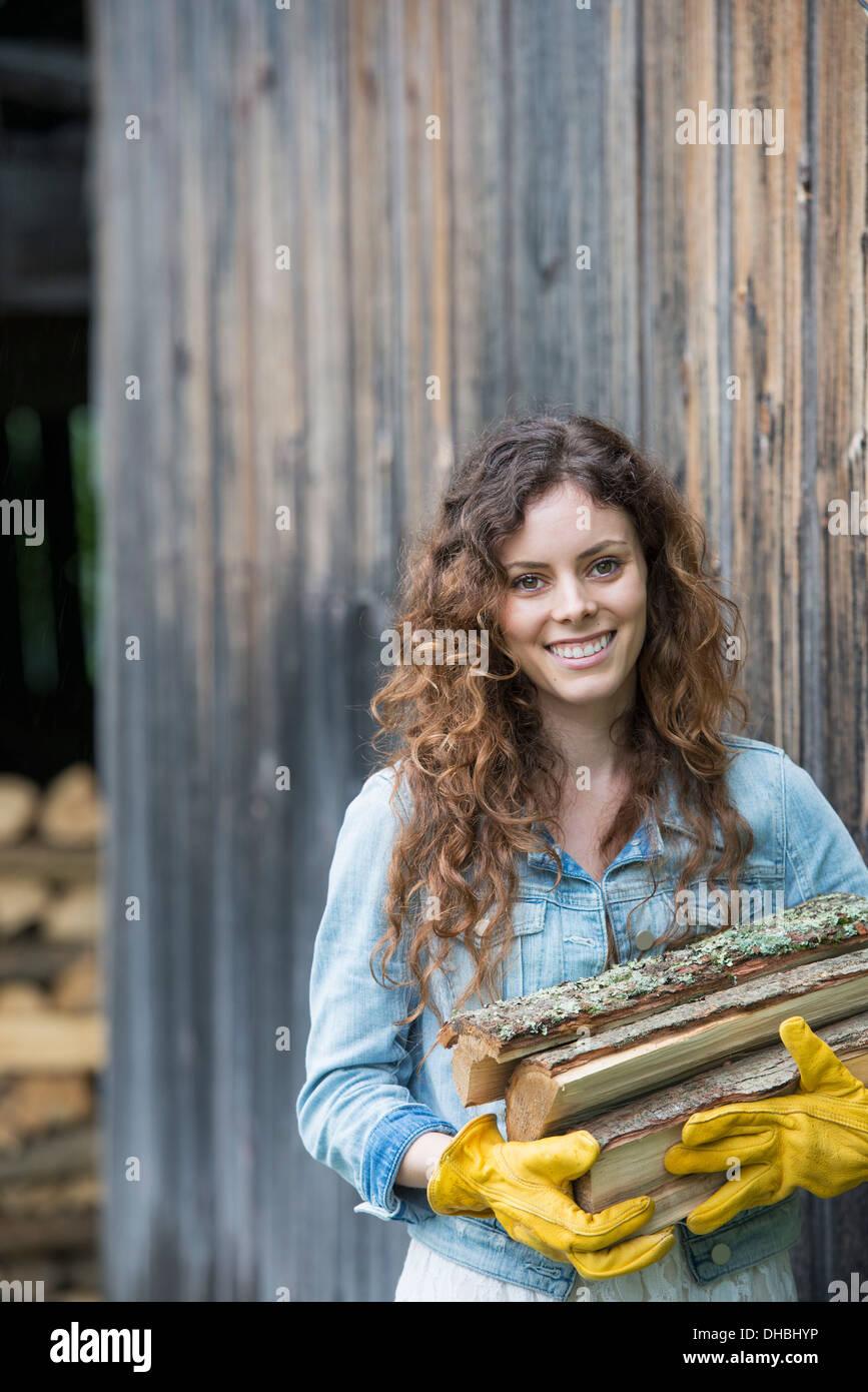 Una donna che porta una bracciata di legna da ardere da logstore nell'azienda. Immagini Stock