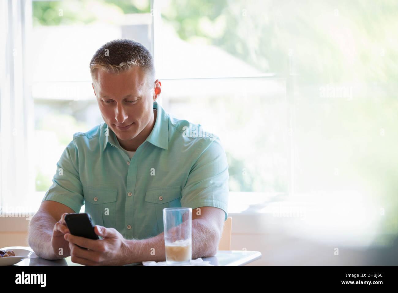 Un uomo con corti capelli ritagliata seduti ad un tavolo del bar, utilizzando un telefono intelligente. Immagini Stock