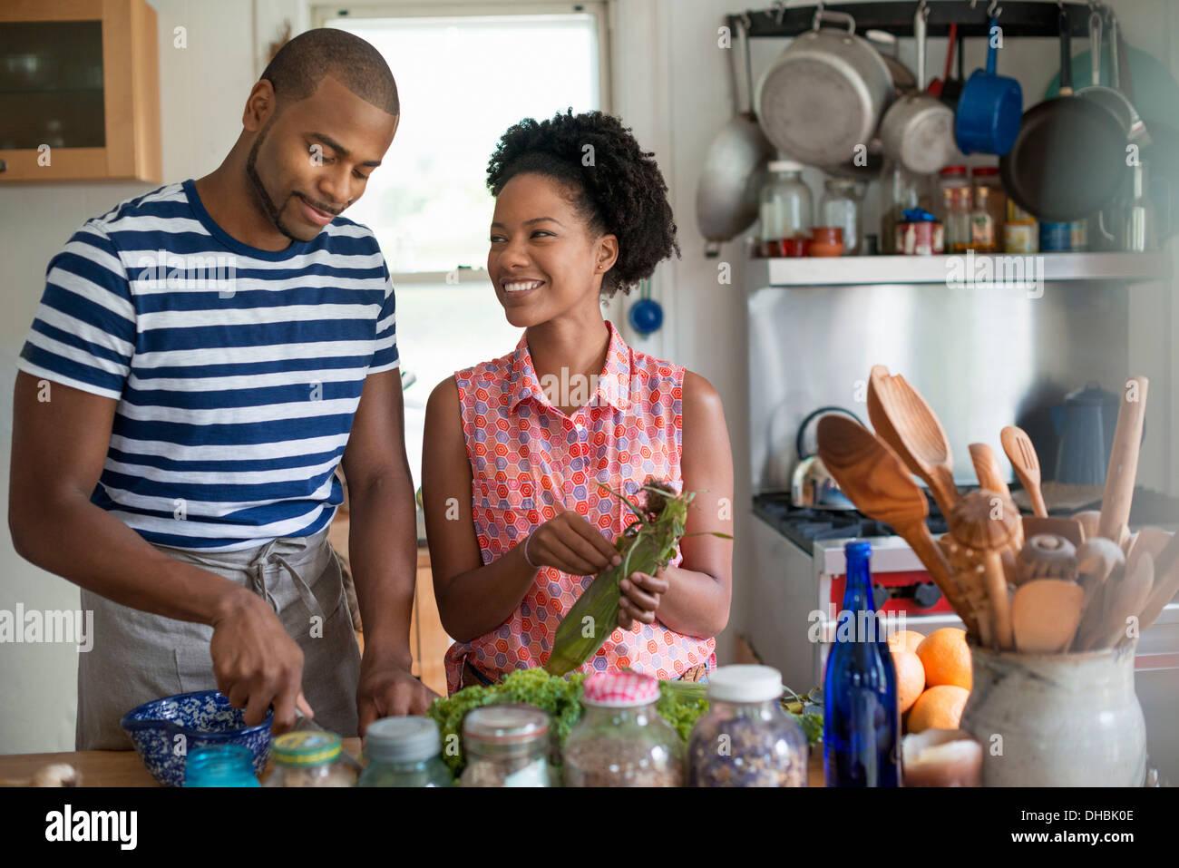 Stile di vita. Due persone che lavorano in una casa colonica in cucina. Immagini Stock