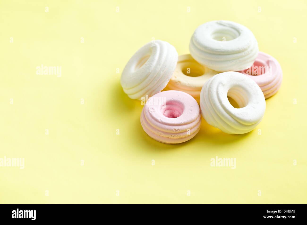 Meringhe colorate su sfondo giallo Immagini Stock