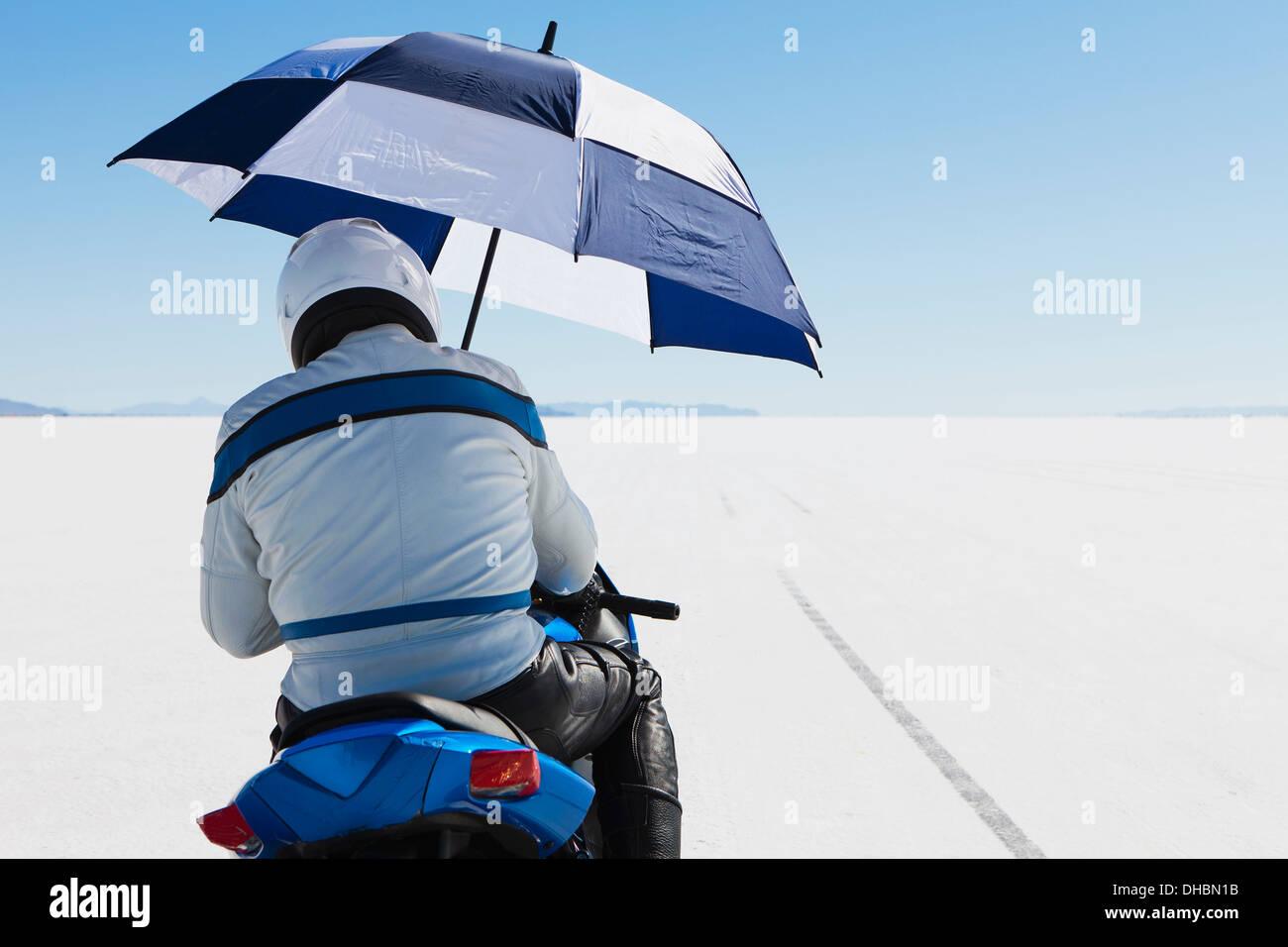 Un motociclista rifugiandosi sotto un ombrello, sulla linea di partenza alla Speed Week, sul Bonneville Saline. Immagini Stock