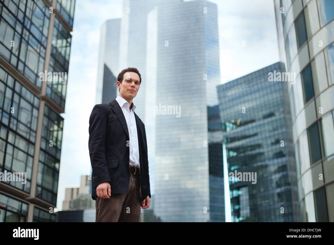 Giovane uomo d affari su edifici di uffici sullo sfondo Immagini Stock