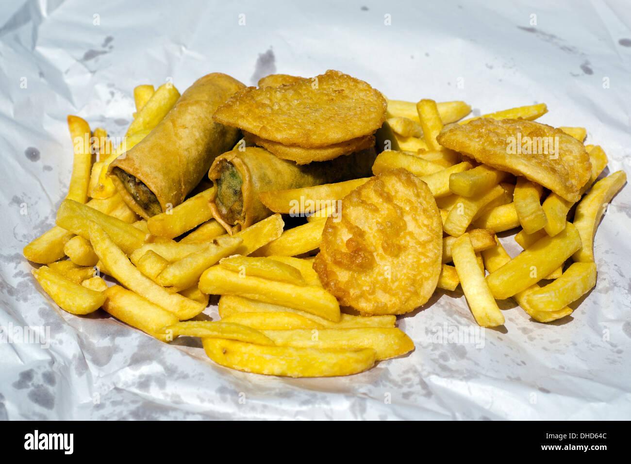 Chips di patata e le frittelle e involtini primavera fast food pasti da asporto piatto all'aperto. Immagini Stock