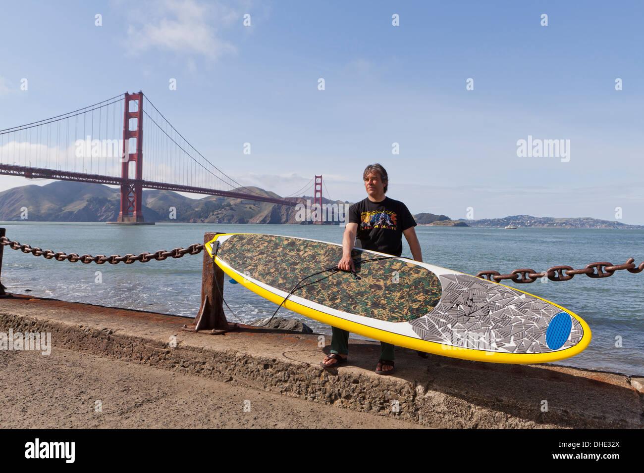 Paddleboard surfer tenendo la scheda - San Francisco, California USA Immagini Stock