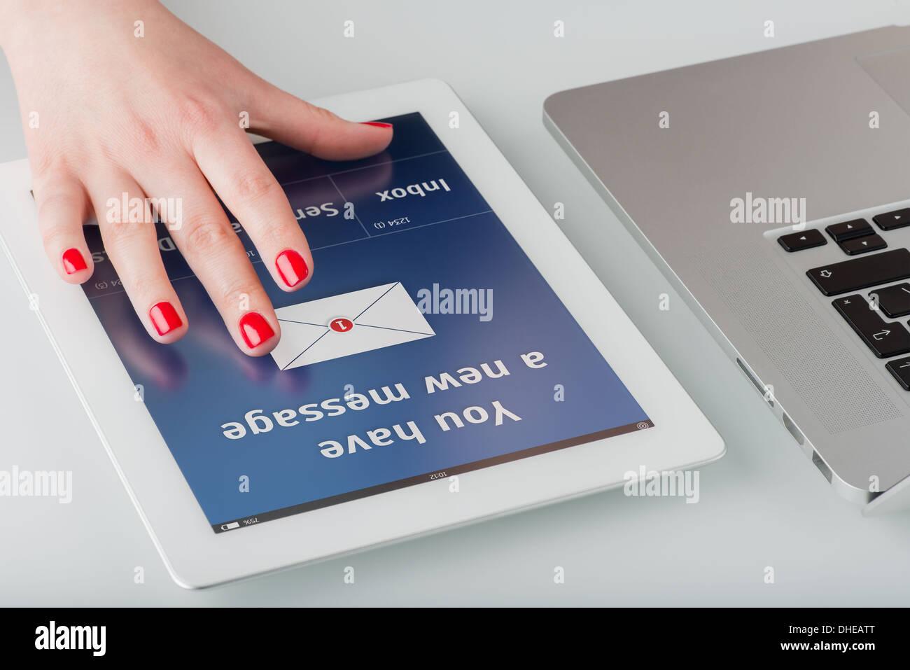 Donna con mano manicure rosso si apre un nuovo messaggio di posta elettronica su un computer tablet. Immagini Stock
