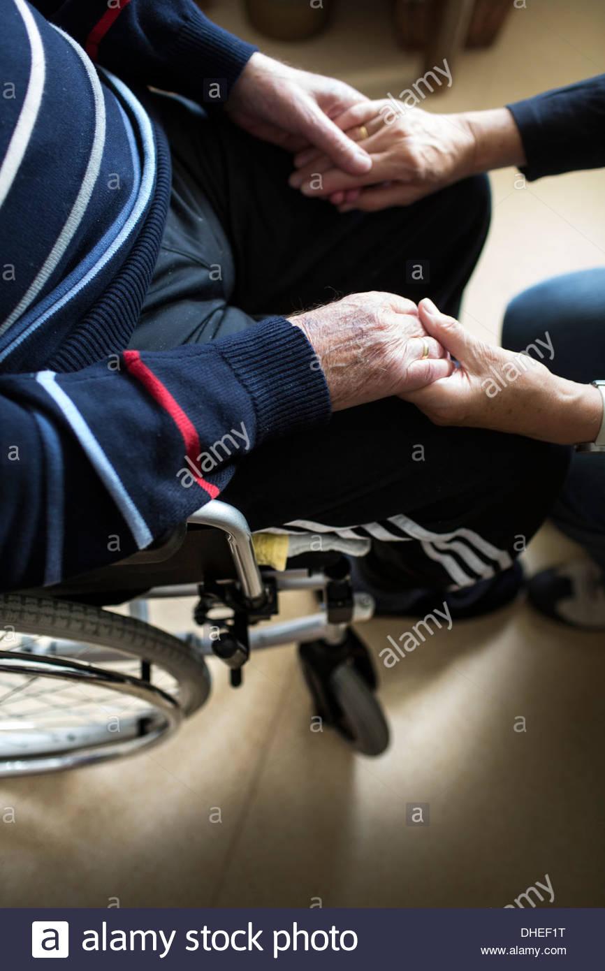Senior donna tenendo le mani di suo marito malato in una casa di cura Immagini Stock
