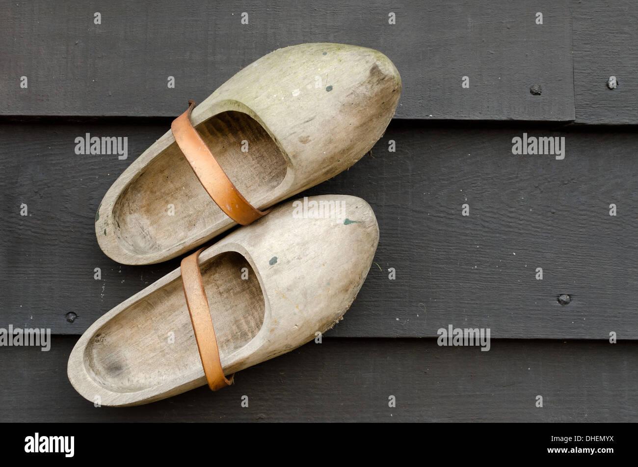 Coppia di tradizionali olandesi giallo scarpe di legno su un legno nero tabella Immagini Stock