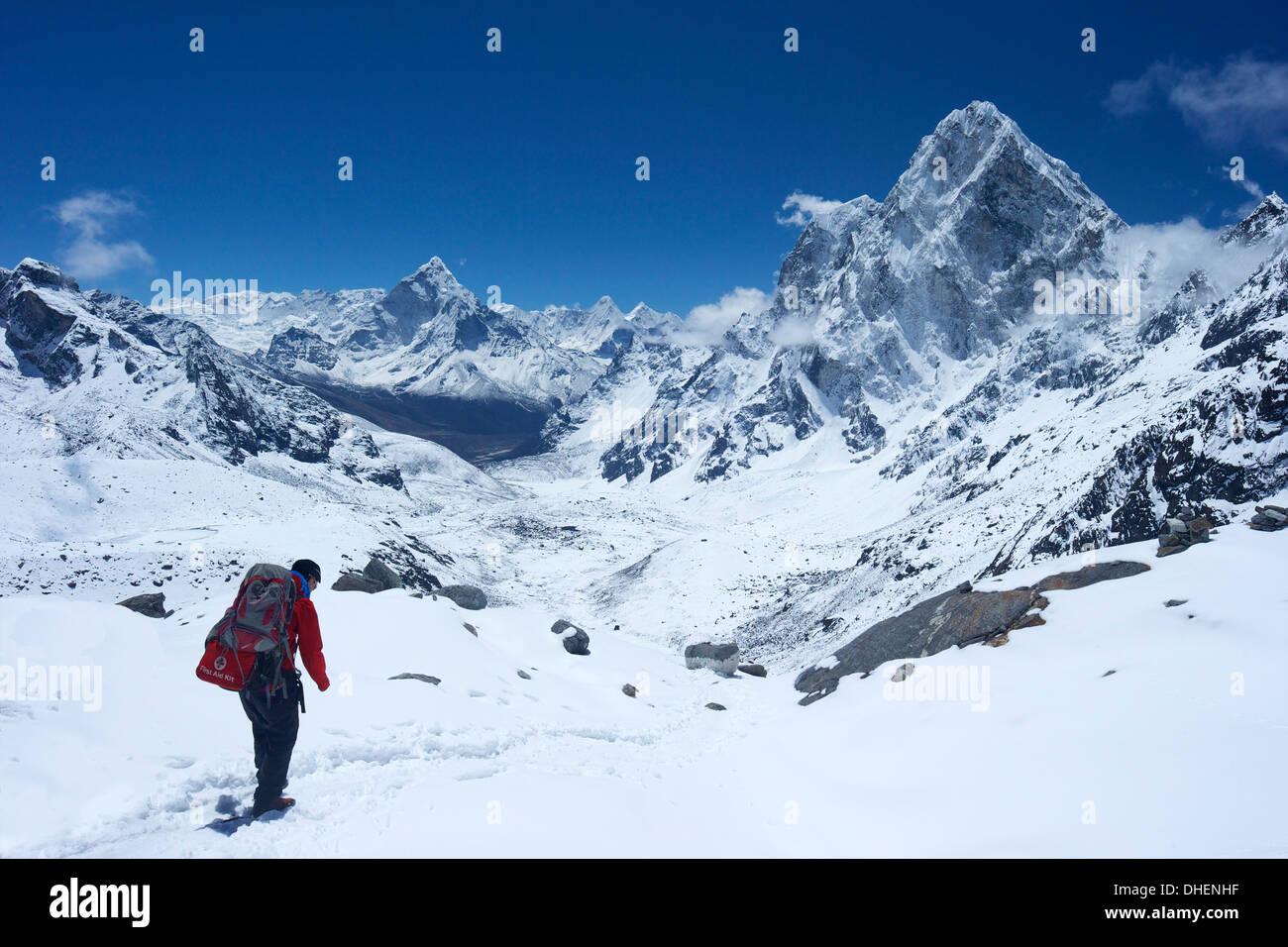 Guida Sherpa camminare su Cho La Pass con Ama Dablam sulla sinistra e Tse Arakam sul lato destro, Nepal, Himalaya Immagini Stock