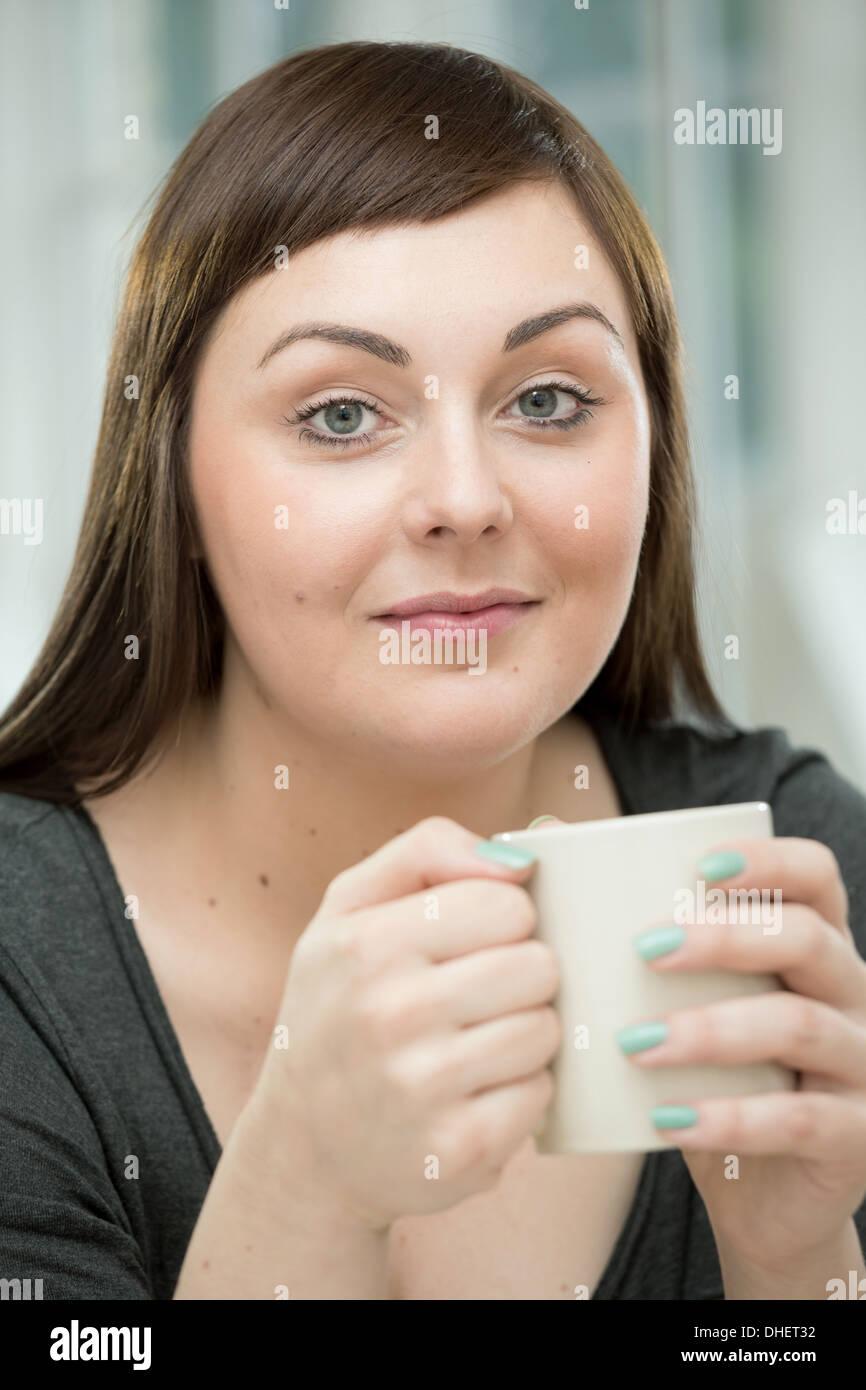 Giovane donna con una tazza di caffè Immagini Stock