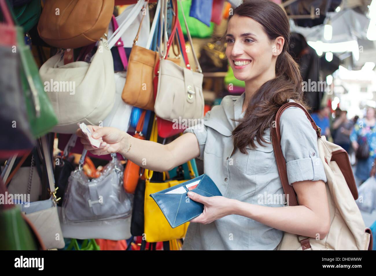 Giovane donna acquisto borsetta, il mercato di San Lorenzo, Firenze, Toscana, Italia Immagini Stock