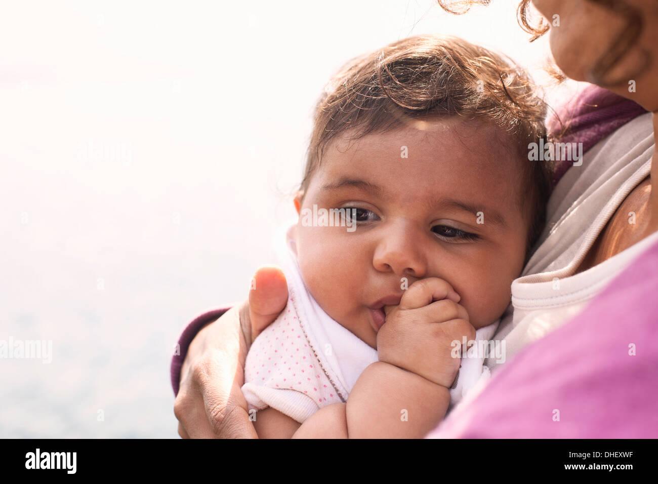 Madre cuddling Baby girl Foto Stock