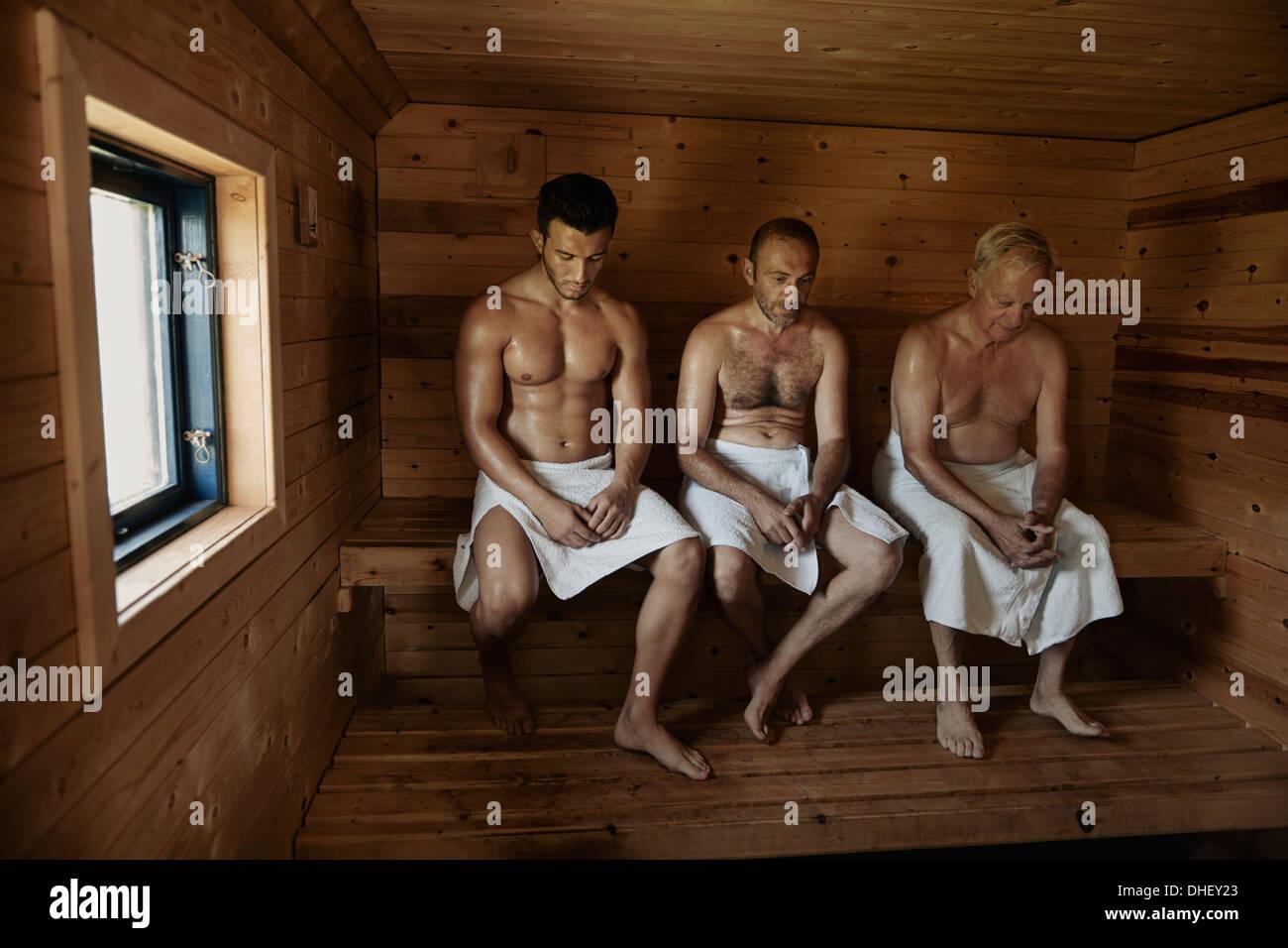 Tre uomini seduti nella sauna con testa inchinata Immagini Stock
