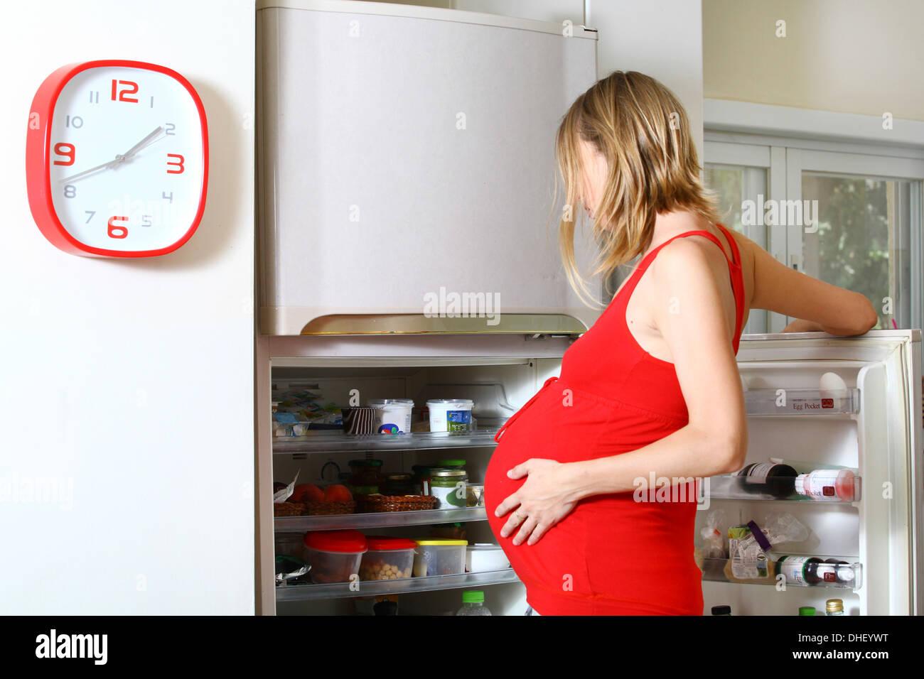 Donna incinta con craving cercando in frigo Immagini Stock