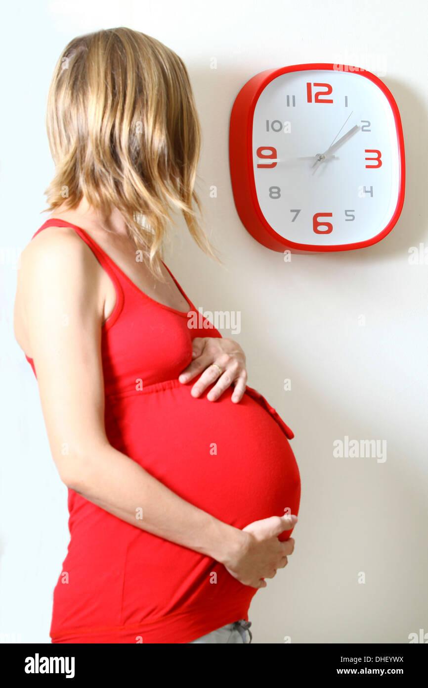 Incinta donna orologio guardando in cucina Immagini Stock