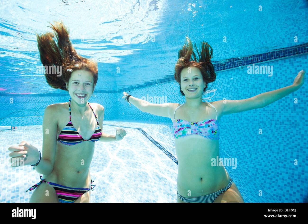 Due ragazze adolescenti nuoto sott'acqua in piscina Immagini Stock