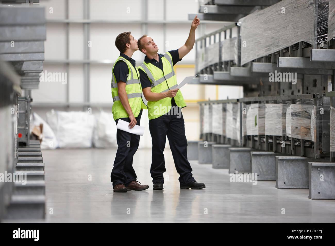 Gli addetti al magazzino ripiani di controllo nel magazzino di ingegneria Immagini Stock