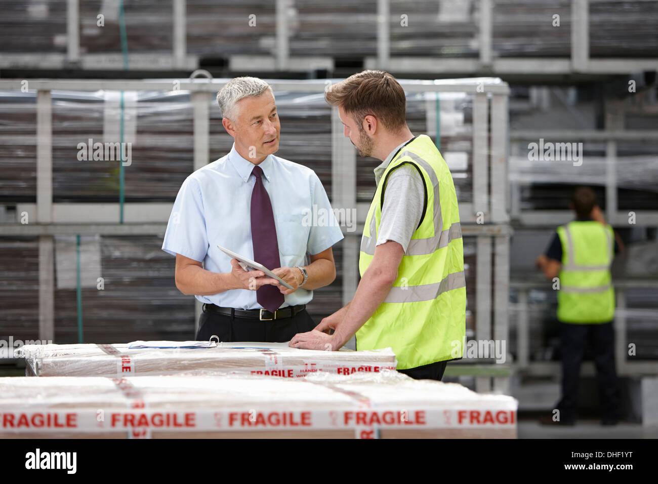 Lavoratore di magazzino e manager a discutere di ordine nel magazzino di ingegneria Immagini Stock