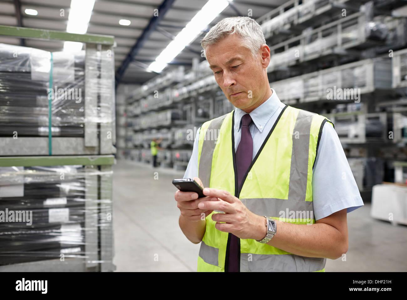 Ritratto di manager utilizzando il telefono cellulare nel magazzino di ingegneria Immagini Stock