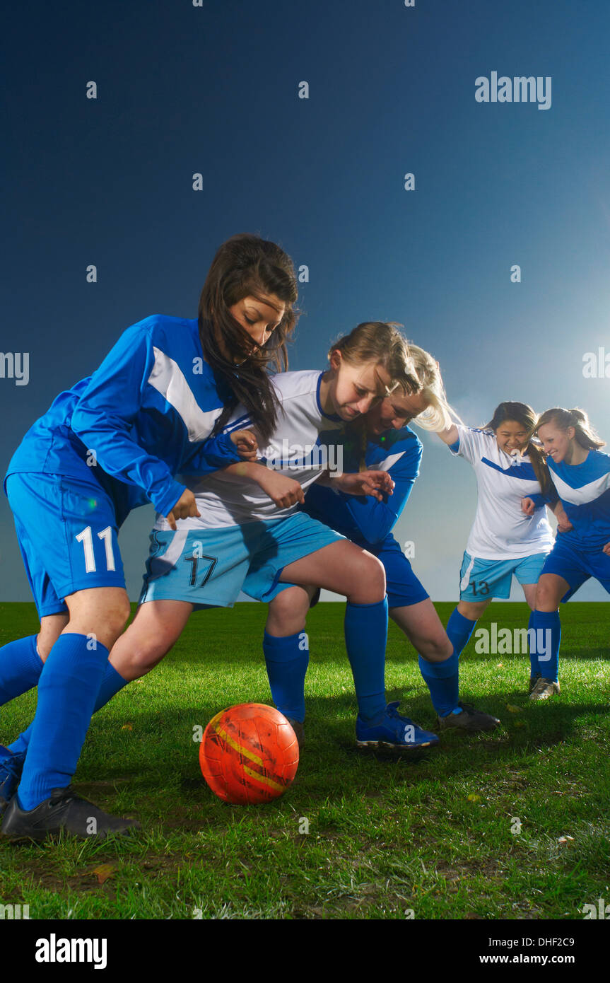 Le giovani donne a giocare il gioco del calcio Immagini Stock