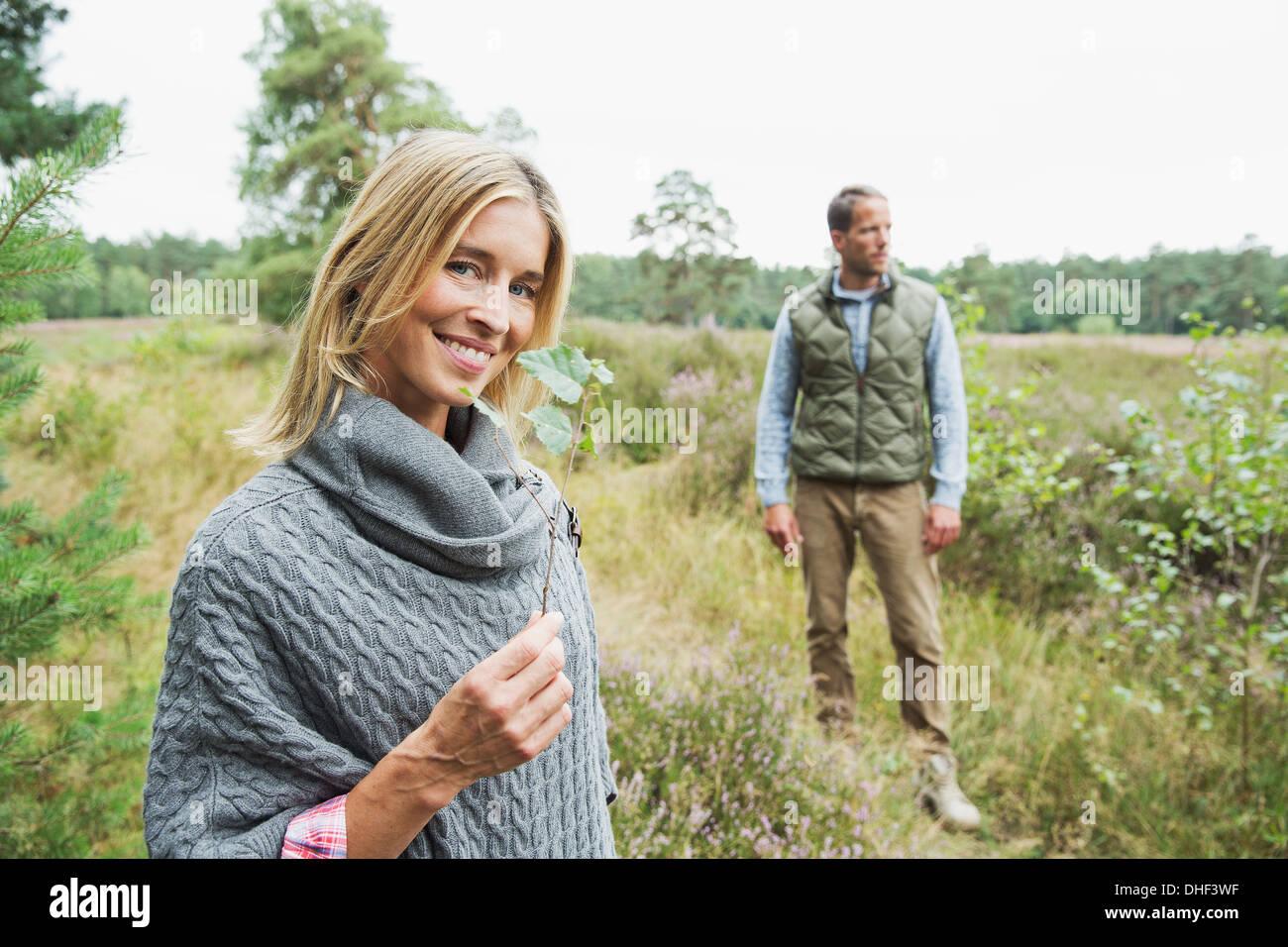 Metà donna adulta holding foglia, uomo in background Immagini Stock