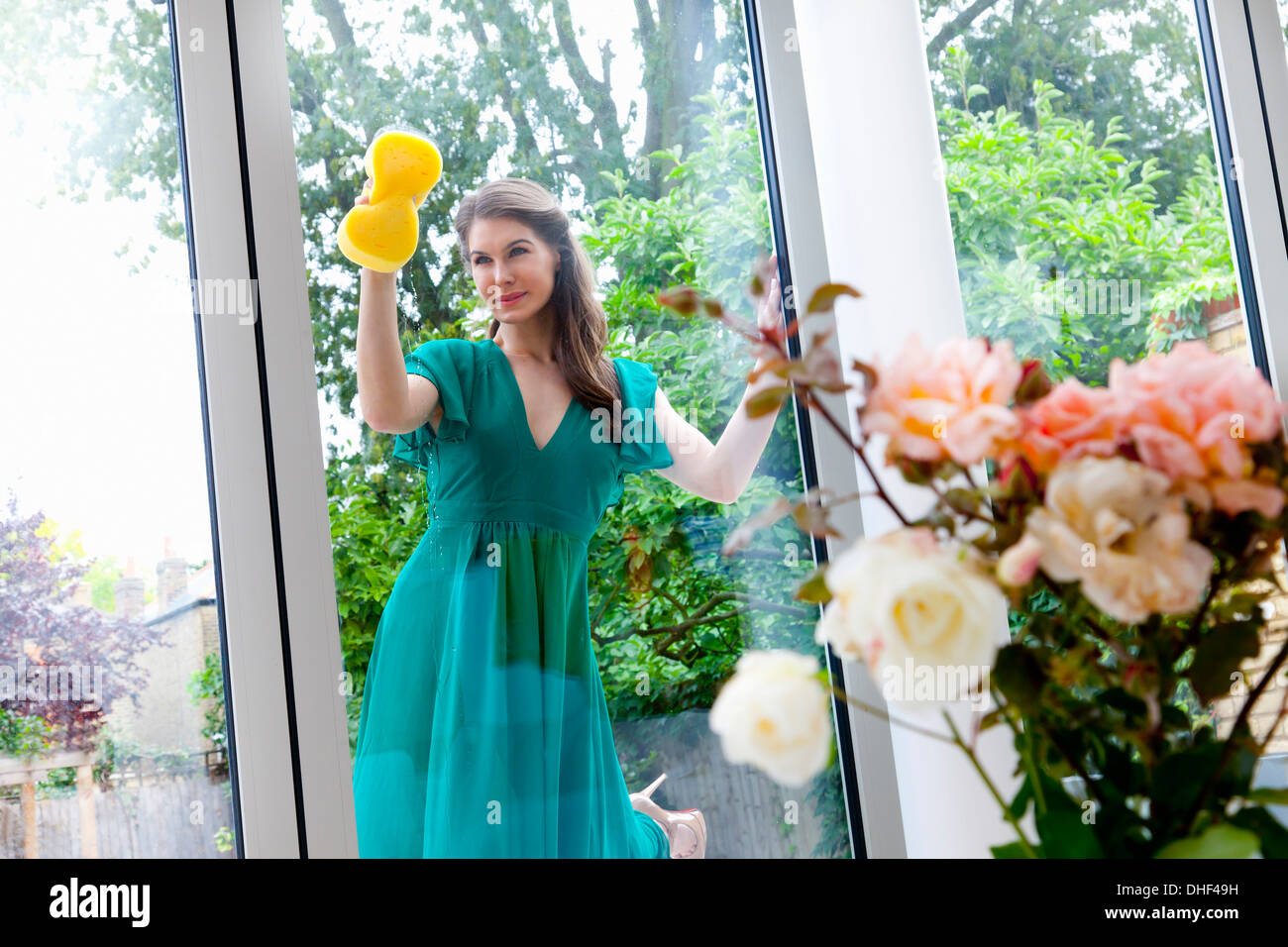 Giovane donna pulizia porta di patio Immagini Stock