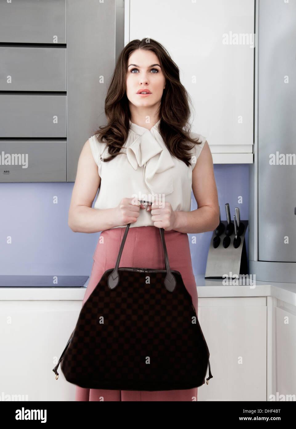 Ritratto di giovane donna holding borsetta con espressione vuota Immagini Stock