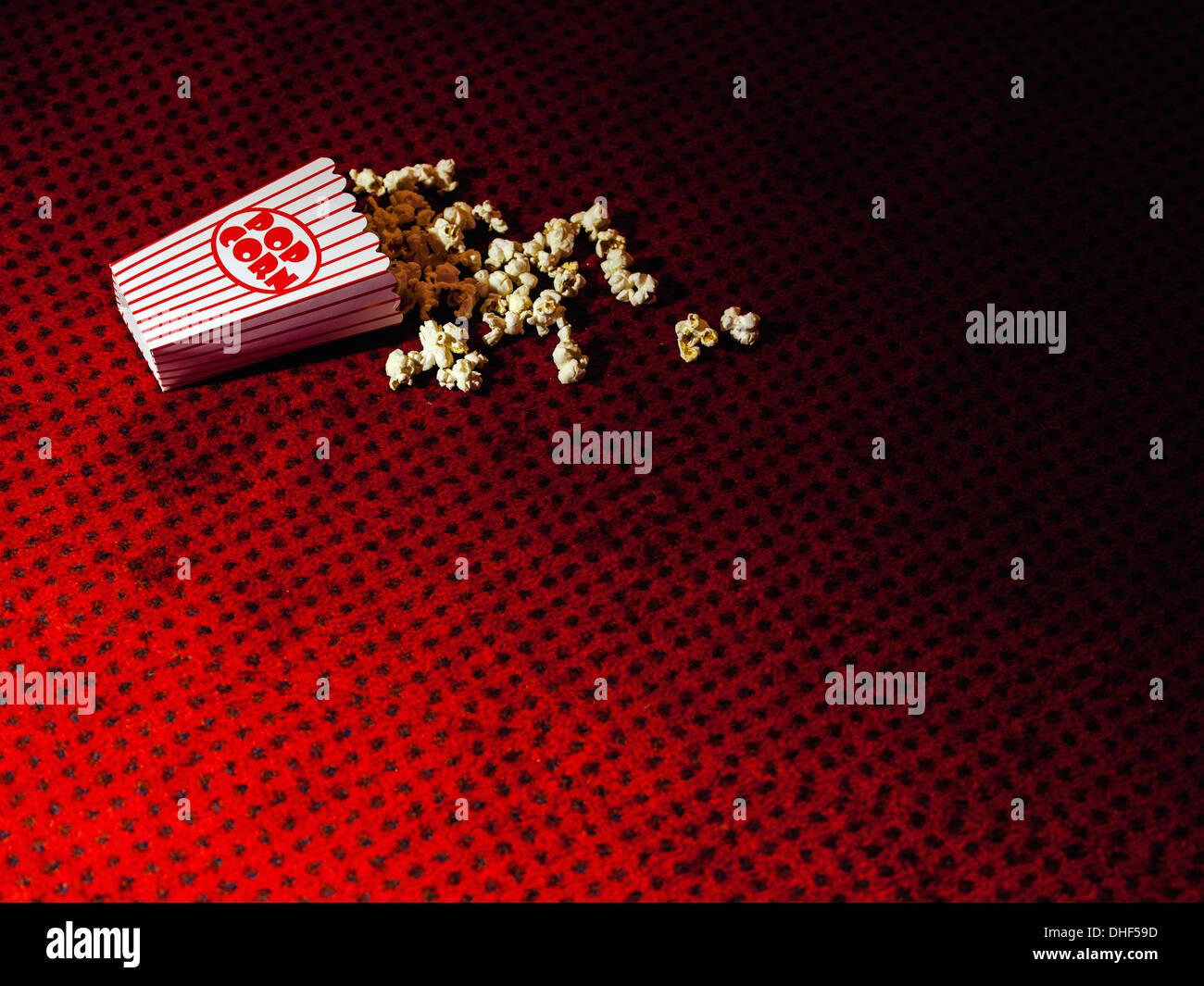 Eventuali fuoriuscite di cartone di popcorn sul tappeto del cinema Immagini Stock