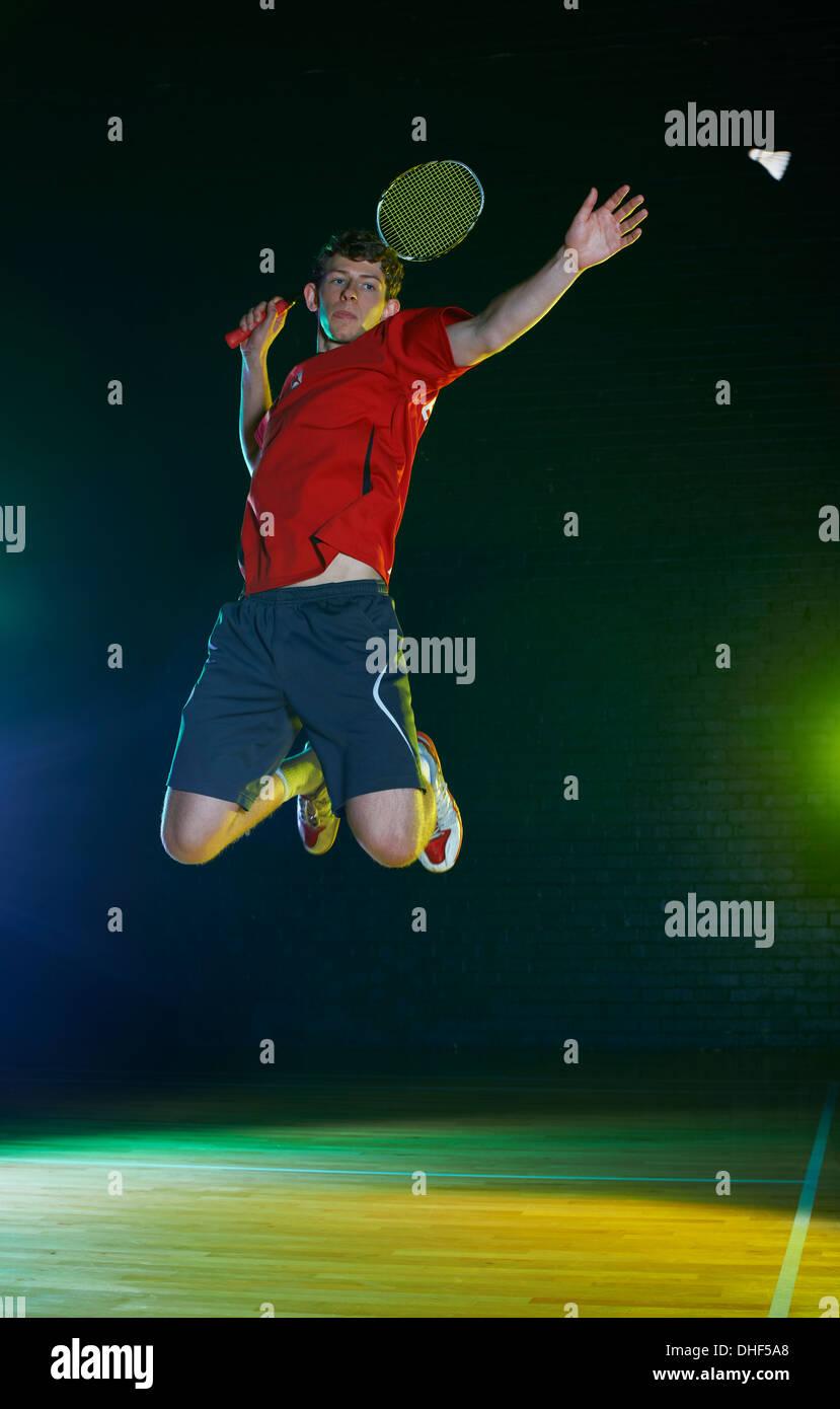 Giovane maschio badminton player mezza aria su corte Immagini Stock