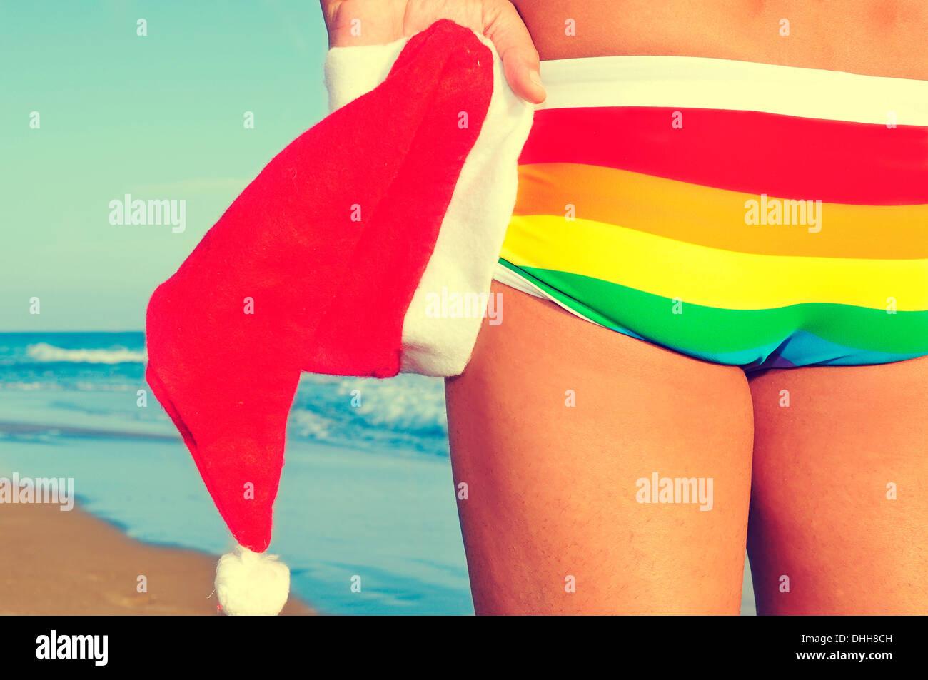 Qualcuno in spiaggia che indossa un costume da bagno arcobaleno e tenendo un cappello da Babbo Natale in mano Immagini Stock