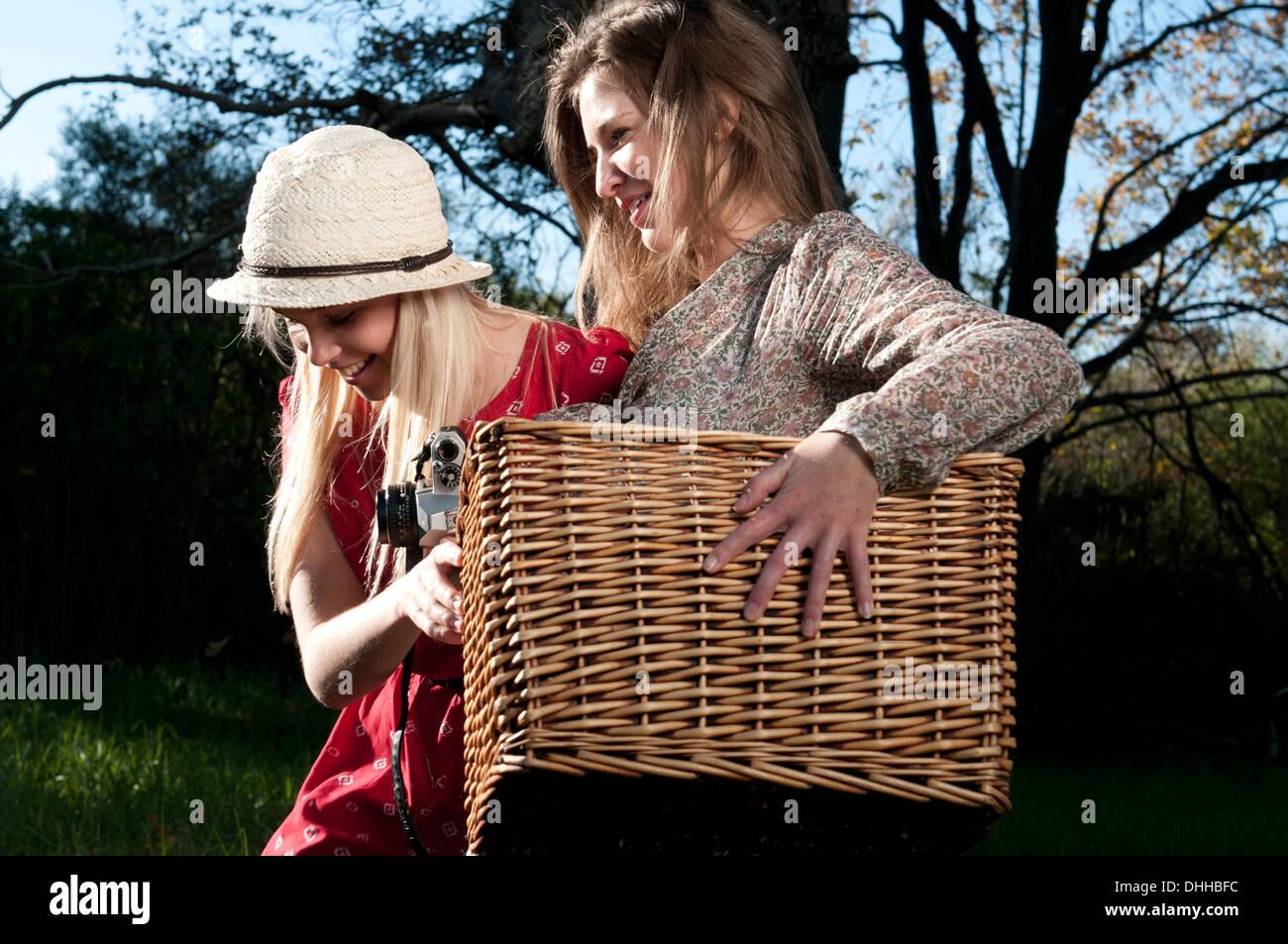 Giovani donne che portano un cestino picnic Immagini Stock