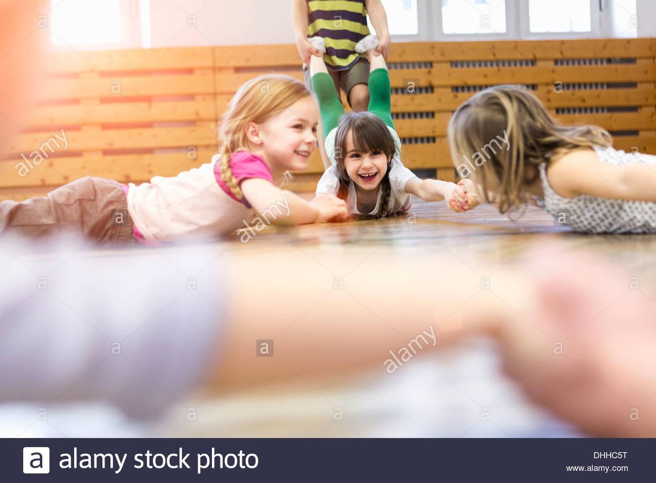 Bambini giacente su fronti giocando il gioco di trazione Foto Stock