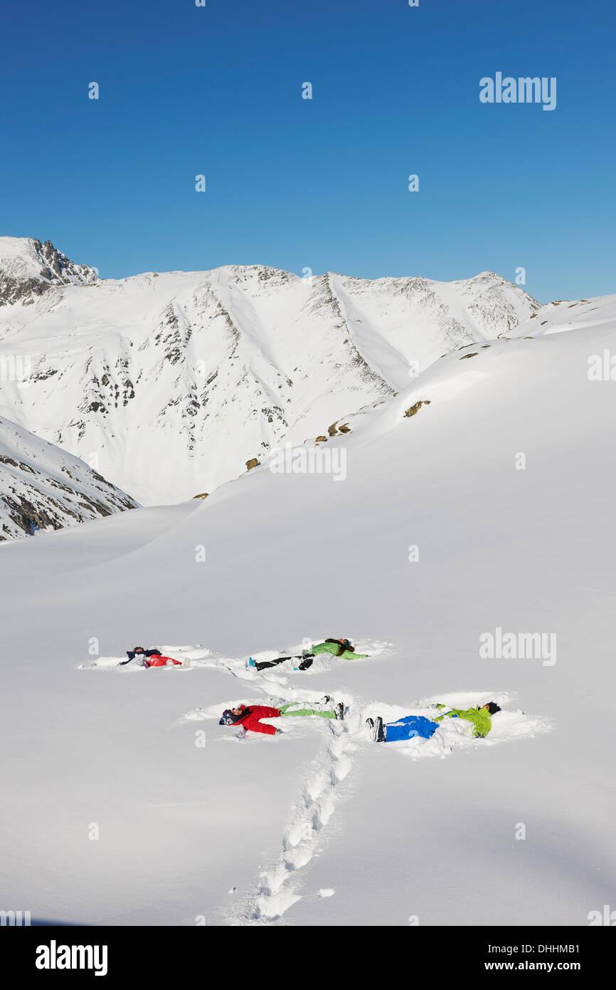 Amici rendendo gli angeli di neve, Kuhtai, Austria Immagini Stock