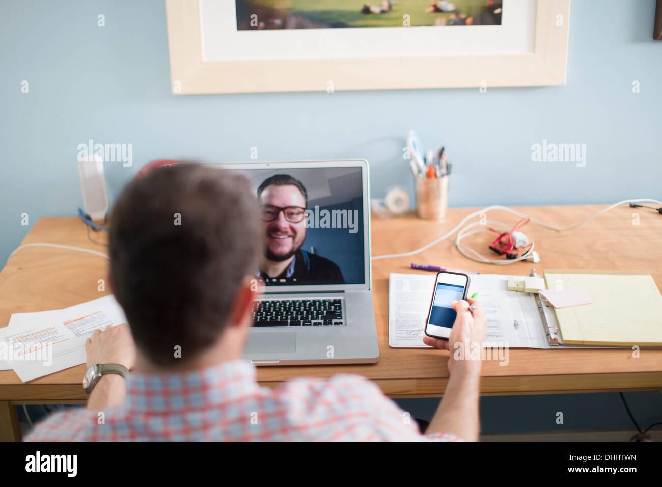 Uomo seduto alla scrivania facendo chiamata video Immagini Stock