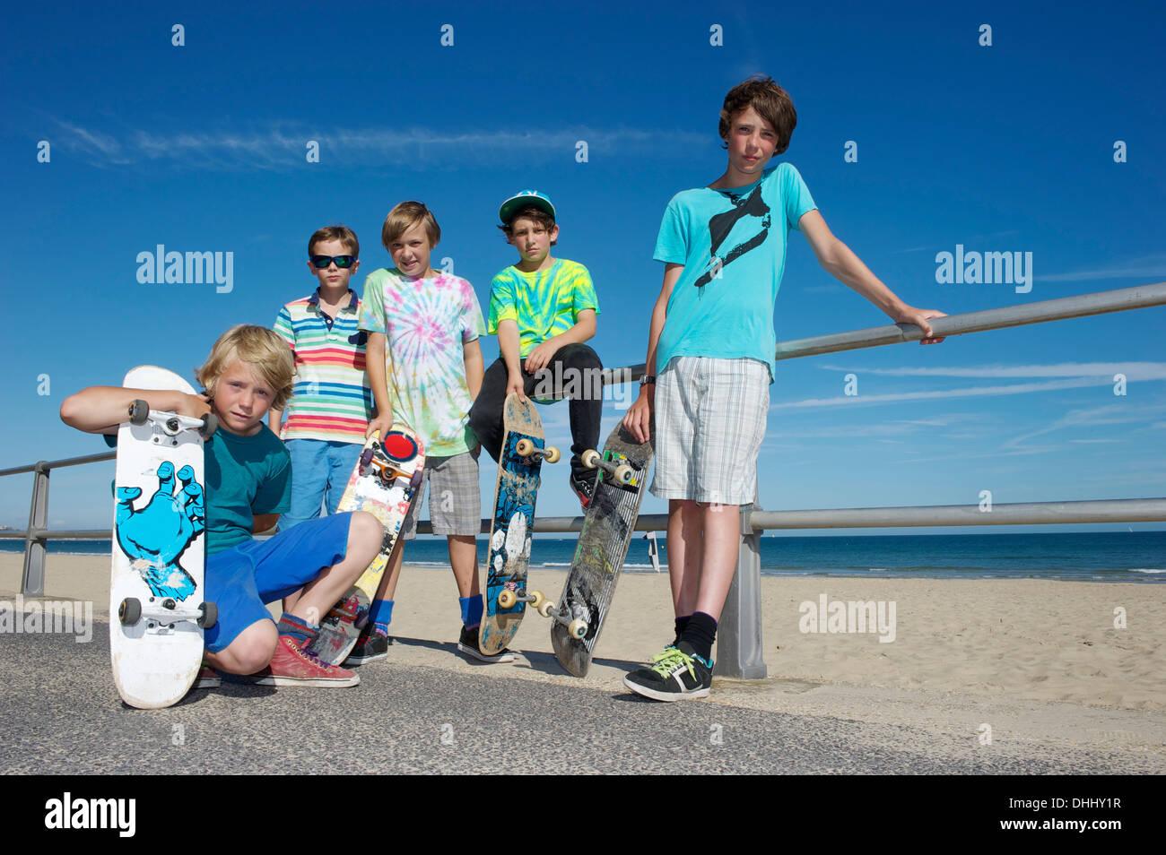 Ritratto di cinque ragazzi con skateboard a costa Immagini Stock