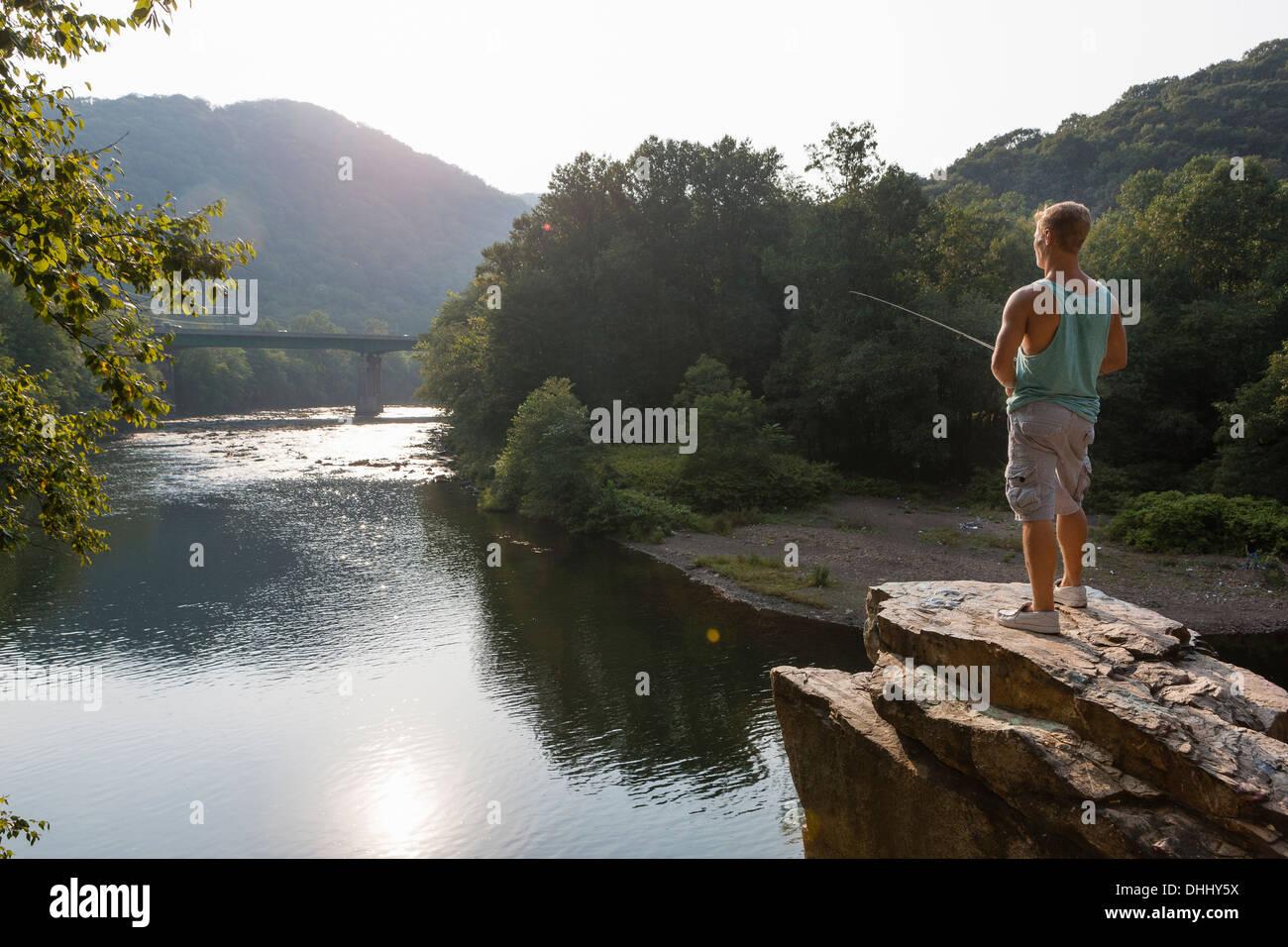 Giovane uomo la pesca dalla sporgenza di roccia, Amburgo, Pennsylvania, STATI UNITI D'AMERICA Immagini Stock