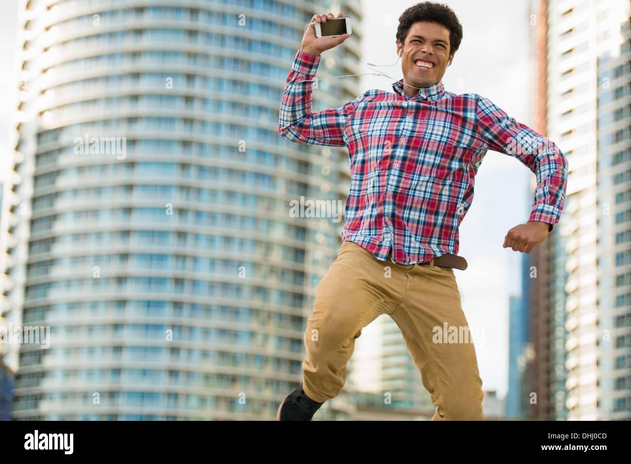 Uomo con telefono cellulare salti di gioia Immagini Stock