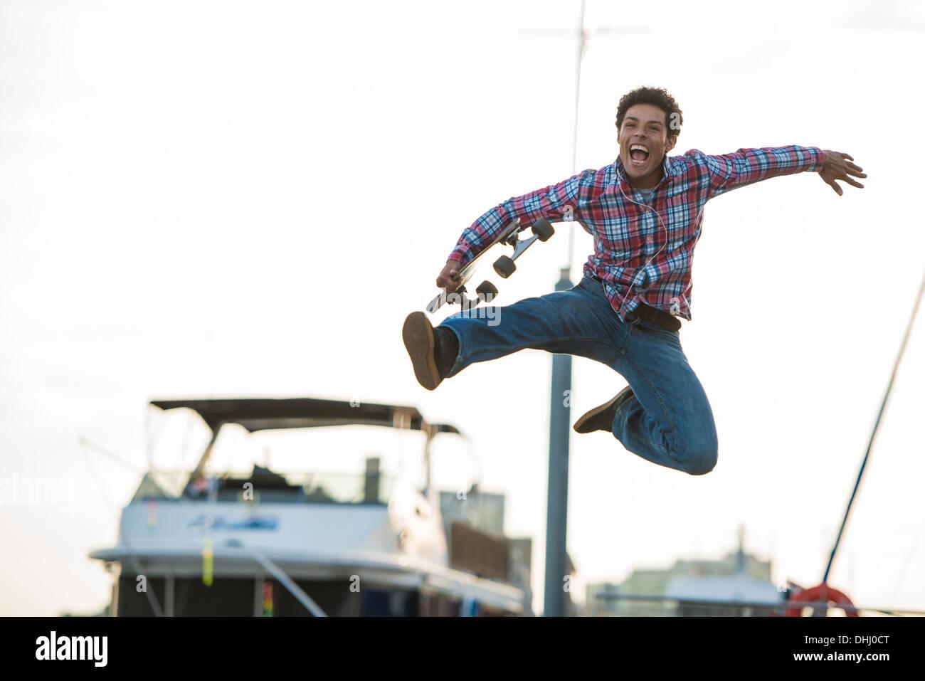 Guidatore di skateboard saltando di gioia Immagini Stock