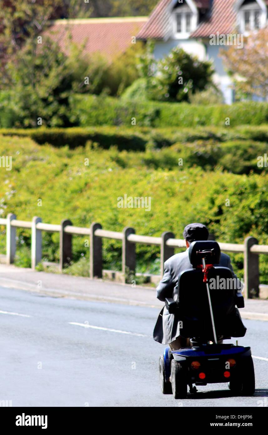 Vista posteriore o senior uomo equitazione scooter di mobilità su strada di campagna. Immagini Stock