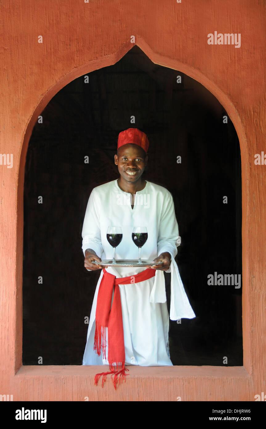 Un cameriere porta due bicchieri di vino rosso. Isola di Benguerra, l'Arcipelago di Bazaruto. Mozambico. Africa orientale. Immagini Stock